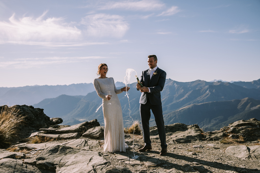 A bride and groom celebrate their wedding by popping some champagne. They are standing on a mountain top, and there are mountains and blue sky behind them. With photography by Alpine Image Company