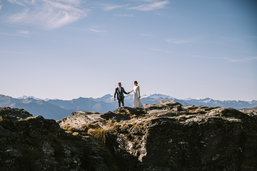A bride and groom hold hands as they walk along a ridge line in the mountains. There are mountains behind them, and the sky is blue. With photography by Alpine Image Company