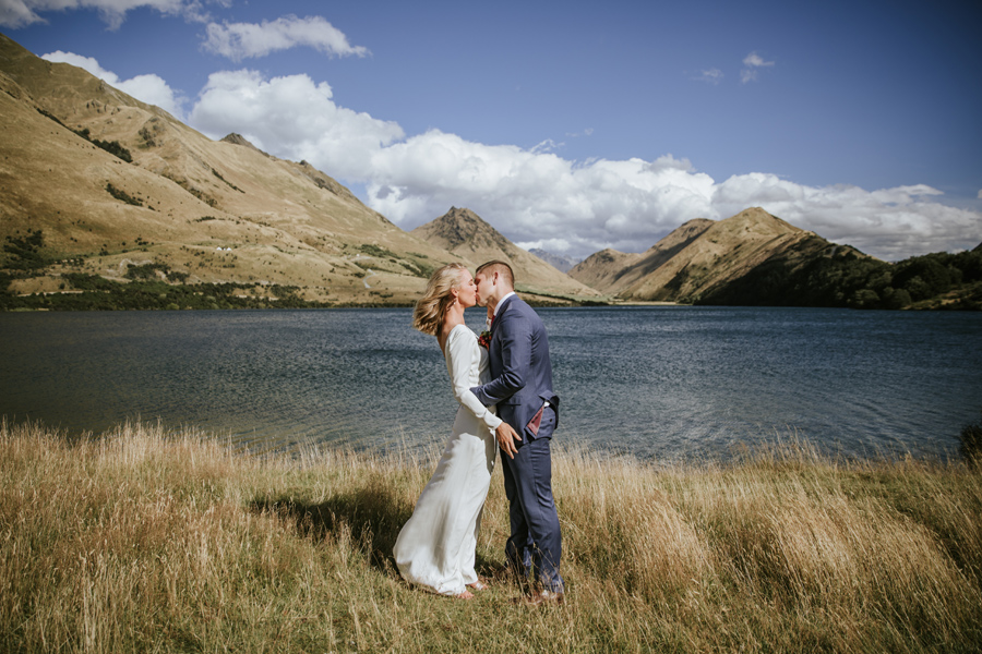 A bride and groom share a kiss on their Queenstown Elopement Wedding. The sky is blue, and they stand in front of a blue lake, with mountains in the distance. Photography by Alpine Image Company