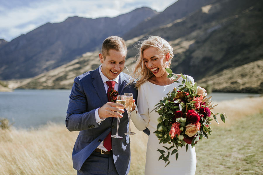 A bride and groom celebrate their Queenstown Elopement Wedding with a glass of champagne. There are mountains in the background, and they are standing in a field by a lake. Photography by Alpine Image Company