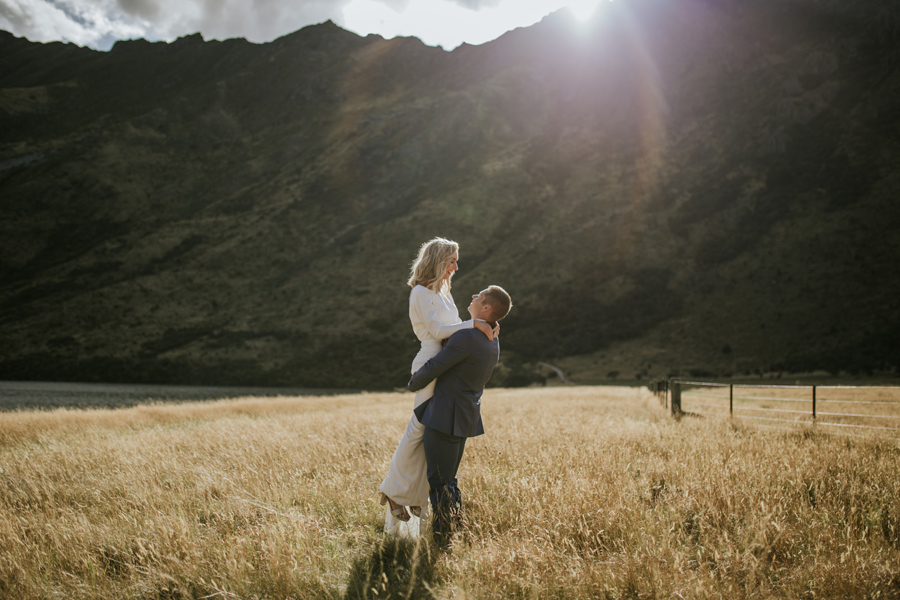 A groom lifts his bride in the air on their Queenstown Wedding Day. They are standing in a field of golden grass, and the sun is setting behind a mountain in the distance. Photography by Alpine Image Company