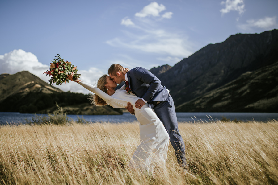A groom dips his bride, who holds her flowers in the air at their Queenstown Elopement Wedding. They stand in a field of golden grass, with a lake and mountains in the distance. Photography by Alpine Image Company