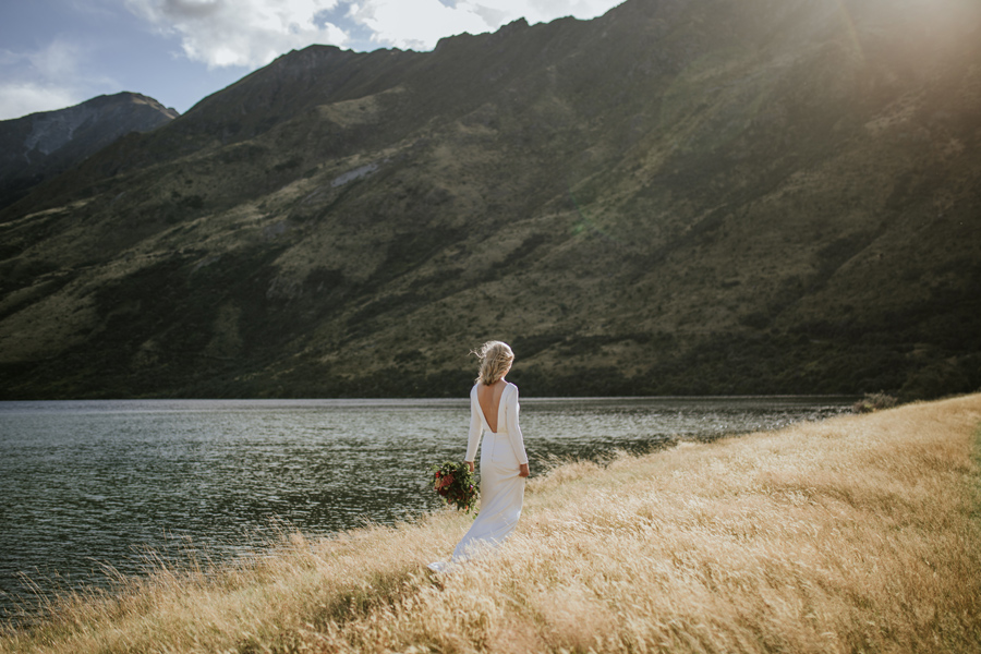 A bride walks through a field of golden grass on her Queenstown Wedding Day. Photography by Alpine Image Company