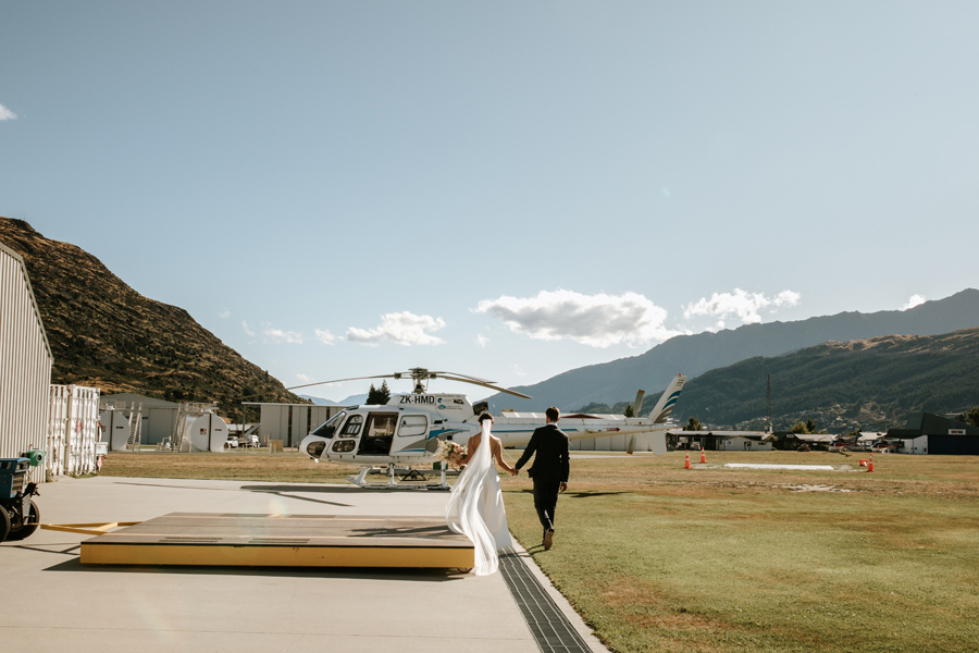 A bride and groom walk towards a helicopter on their Queenstown elopement wedding. With Photography by Alpine Image Company