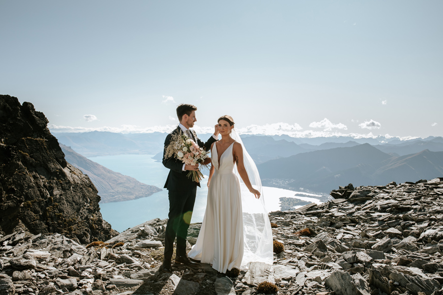 A groom tucks a piece of hair behind his wife's ear. They are standing on a rocky mountain on their Queenstown elopement wedding. With Photography by Alpine Image Company