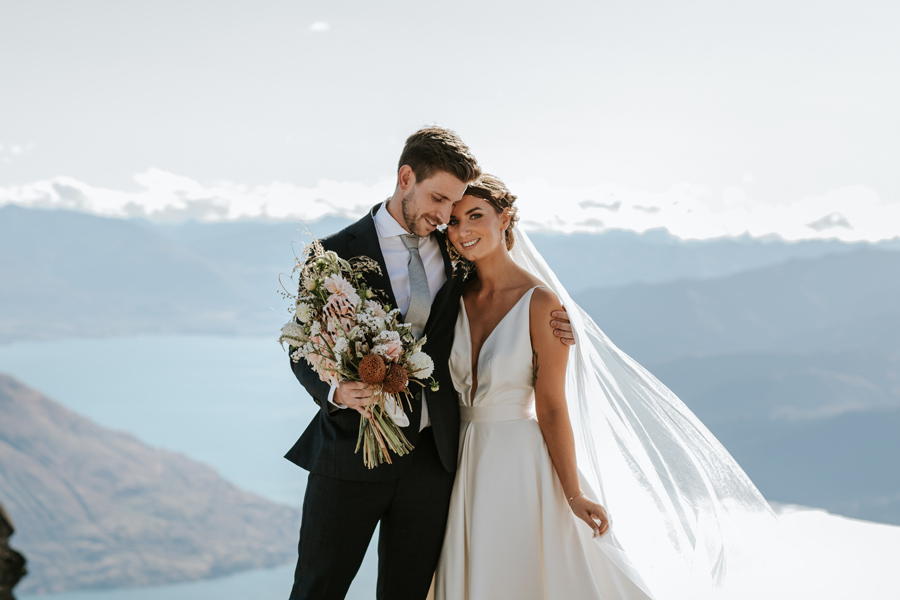 A groom embraces his bride on their Queenstown Elopement Wedding. They are standing on top of a mountain. The sky is blue and there is a lake behind them. With photography by Alpine Image Company