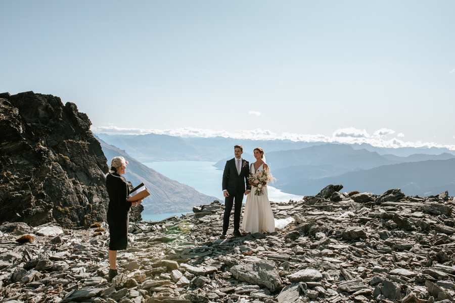 A wedding ceremony on top of The Remarkables on a couple's Queenstown Elopement Wedding. The couple stand facing the celebrant. The sky is blue and there is a lake and mountains in the distance. The mountain is rocky and rugged. With photography by Alpine Image Company