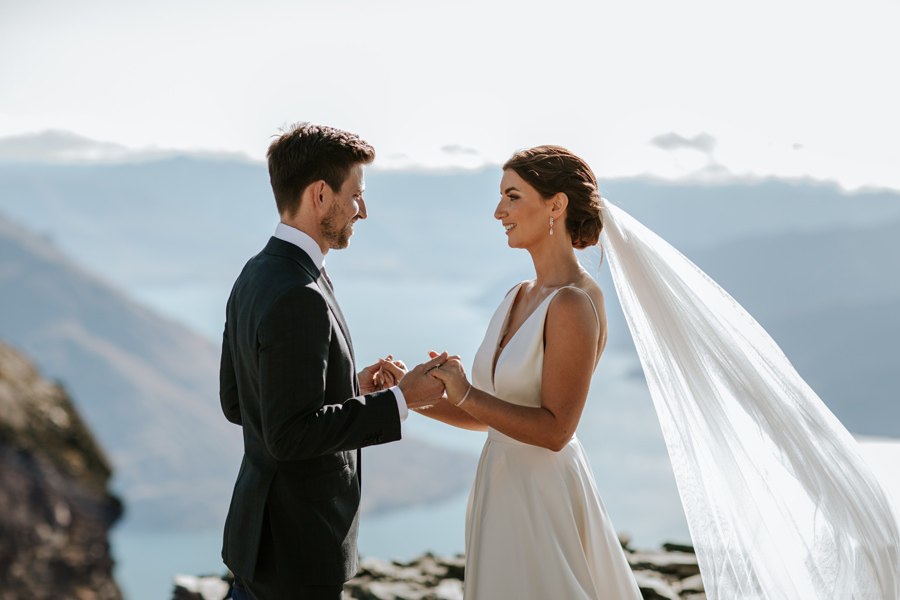 A bride and groom smile at each other during their ceremony on their Queenstown Elopement Wedding. The sky is blue and there are mountains behind them in the distance. With photography by Alpine Image Company