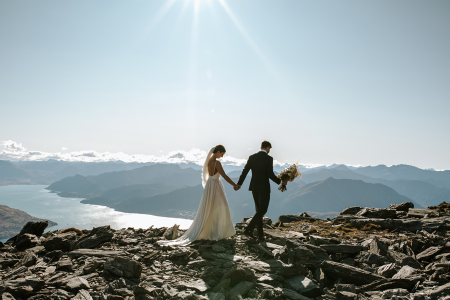 A bride and groom walk along a rocky ridge line on their Queenstown elopement wedding day. The sky is blue and there is a lake and mountains in the distance. With photography by Alpine Image Company.