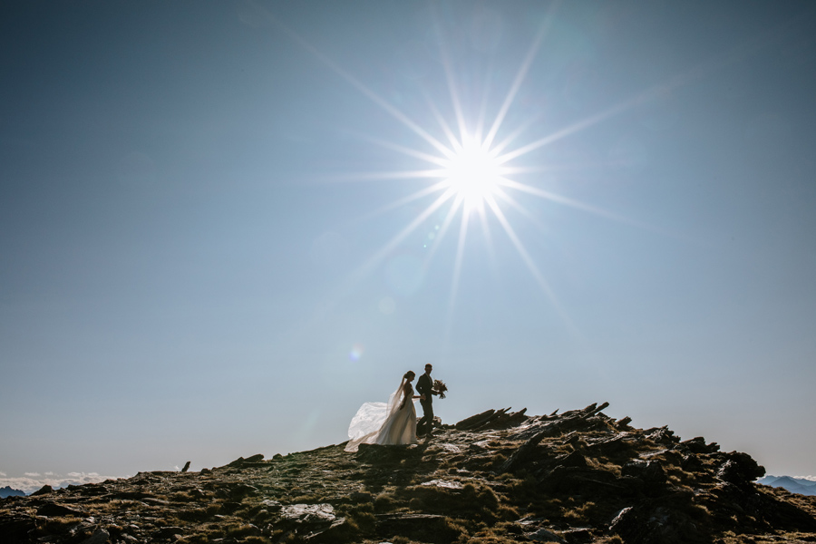 A bride and groom walk up a rocky ridge on their Queenstown Elopement Wedding day. There is sunburst in the sky above them, and the sky is blue. With photography by Alpine Image Company.
