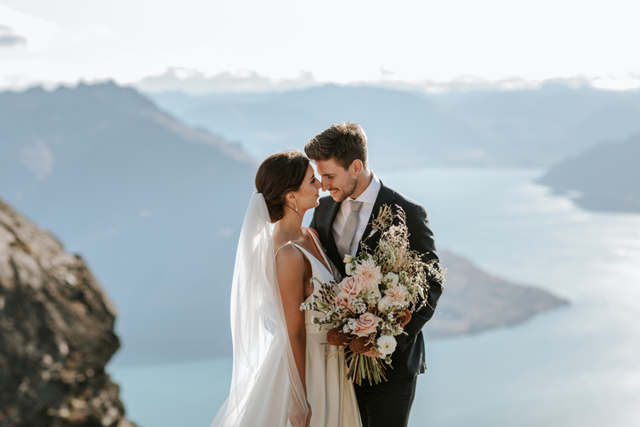 A bride and groom share an intimate moment on a mountain top, on their Queenstown elopement wedding day. The sky is blue and there is a lake and mountains in the distance behind them. With photography by Alpine Image Company