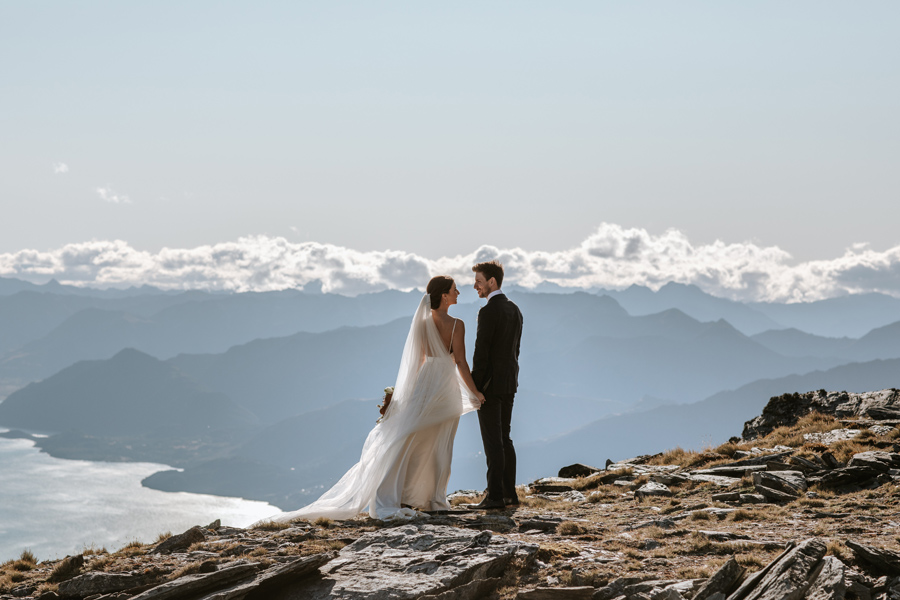 A couple look towards each other as they stand on a mountain overlooking a lake on their Queenstown Elopement Wedding. With photography by Alpine Image Company