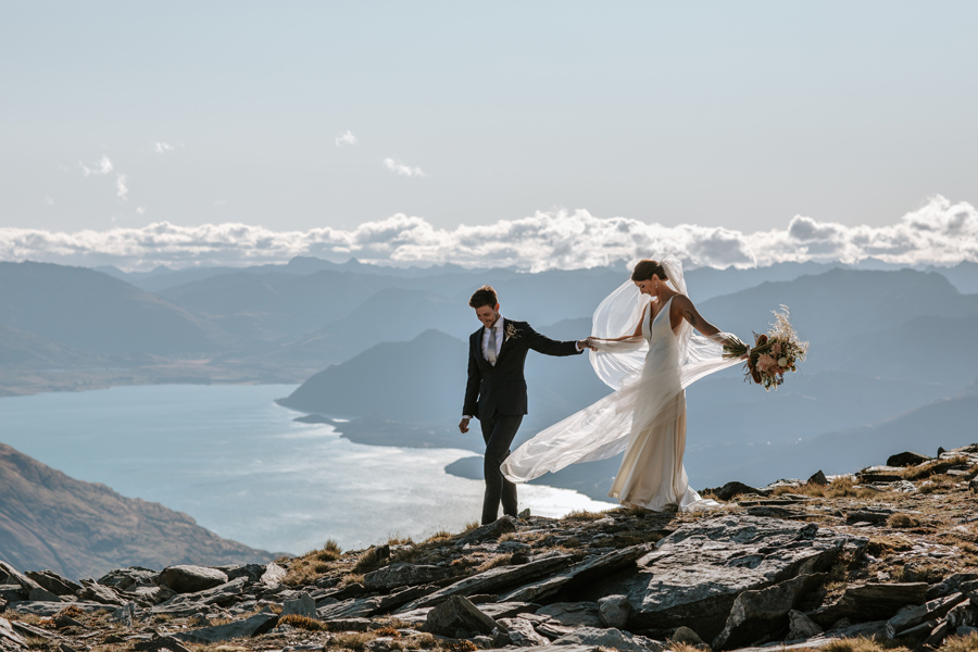A bride and groom walk along a rocky ridge on their Queenstown elopement wedding day. There are mountains in the distance and a blue lake below them. With photography by Alpine Image Company