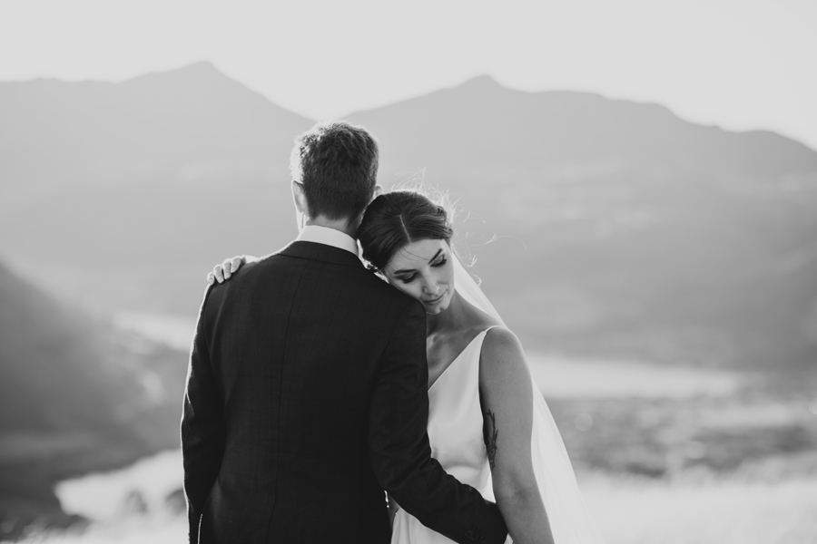 A bride rests her head against her groom on their Queenstown Elopement Wedding day. The image is in black and white. With photography by Alpine Image Company