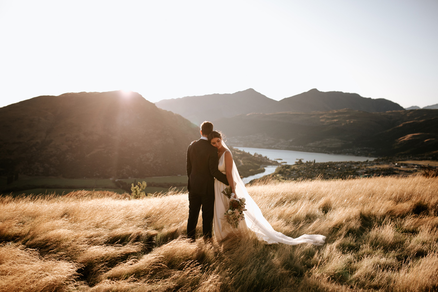 A bride rests her head against her grooms shoulder, as the sun sets behind a mountain on their Queenstown elopement wedding day. They stand in a field of golden grass. With photography by Alpine Image Company