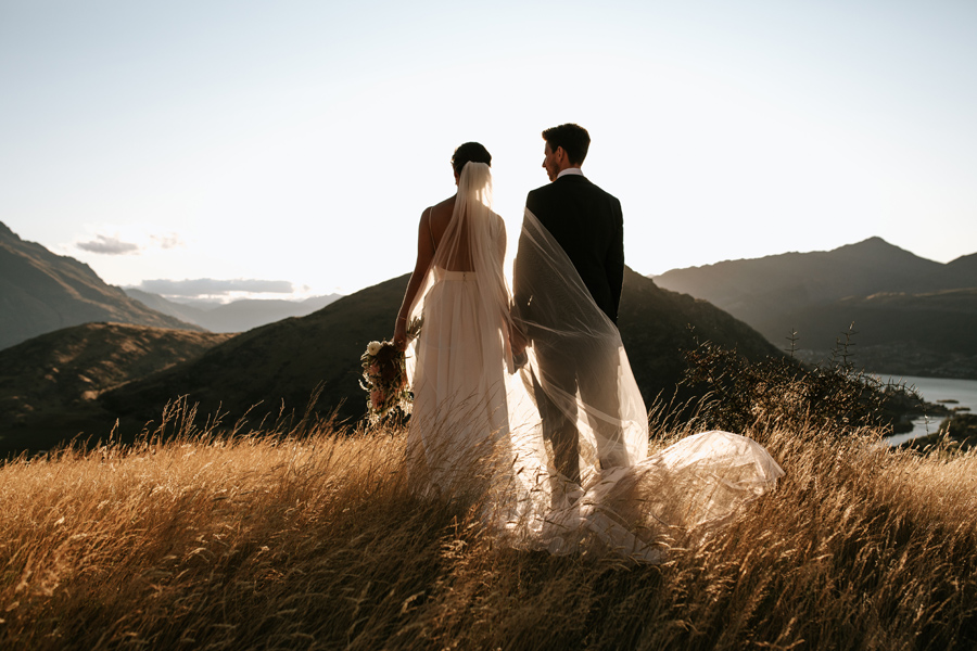 A bride and groom stand looking out at the view on their Queenstown elopement wedding day. The sun is setting and they stand in a field of golden grass. With photography by Alpine Image Company