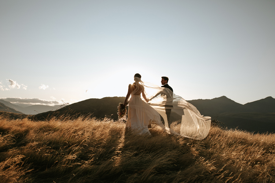 A bride and groom walk in a field of golden grass on their Queenstown wedding day. There are sillouettes of mountains in the distance. With photography by Alpine Image Company