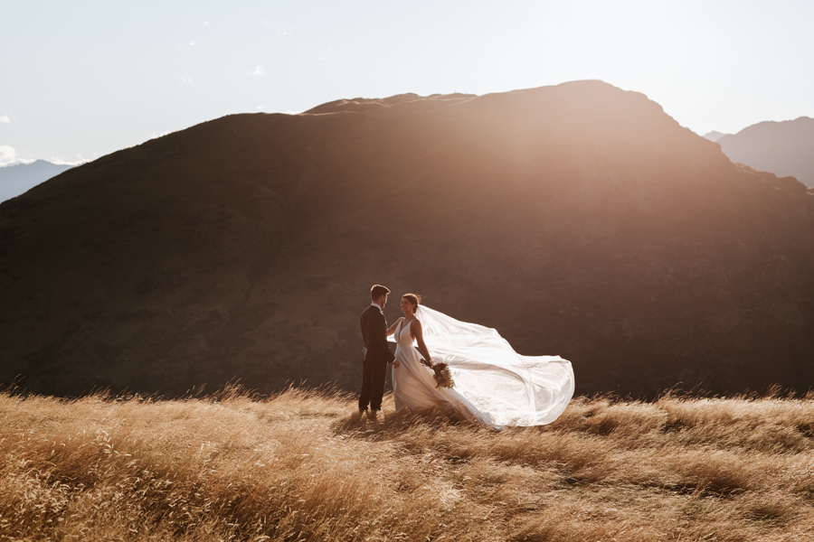 A bride plays with her veil as it flutters in the breeze, on their Queenstown elopement wedding day. The sun is setting behind them, and there are sillouetted mountains in the distance. With photography by Alpine Image Company