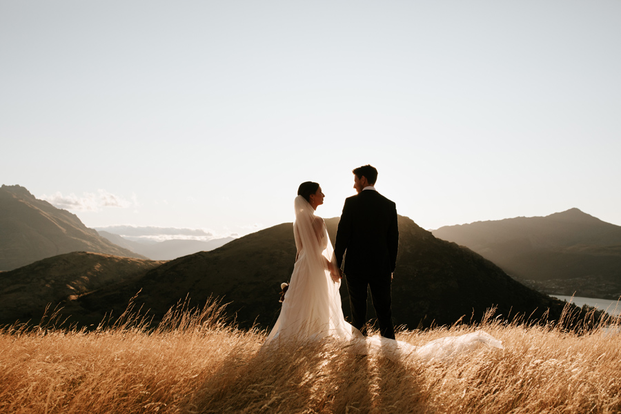 A bride and groom look towards each other, as they stand in a field of golden grass on their Queenstown elopement wedding day. With photography by Alpine Image Company