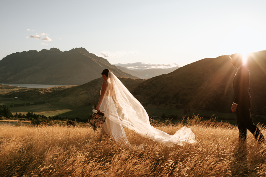 A bride and groom walk through a field of golden grass on their Queenstown elopement wedding day. With photography by Alpine Image Company
