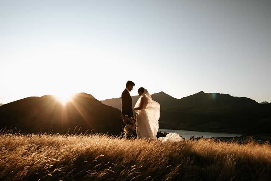 A bride and groom stand in a field of golden grass on their Queenstown elopement wedding. The sun is setting and the mountains in the distance are in sillouette. With photography by Alpine Image Company