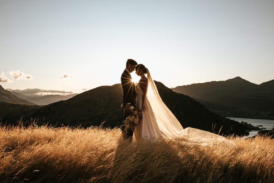 A bride and groom rest their heads together in a field of golden grass on their Queenstown elopement wedding day. There is a starburst between their heads. The sky is blue and the mountains are sillouetted in the distance. With photography by Alpine Image Company