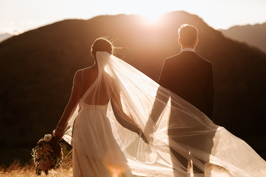 A couple look out towards the setting sun, on their Queenstown elopement wedding day. The mountains are in sillouette and the brides veil flows in the breeze. With photography by Alpine Image Company