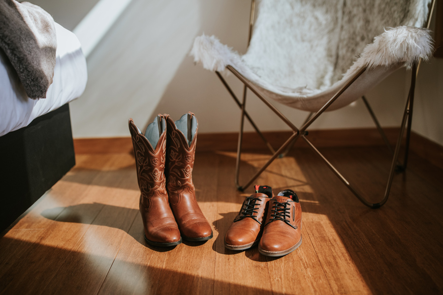 Cowboy boots and mens dress shoot on a wooden floor. Waiting for their owners to put them on for the wanaka elopement wedding. With photography by Alpine Image Company