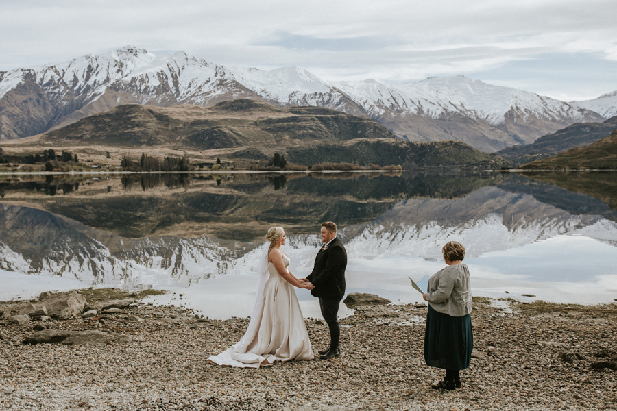 A couple face each other at their ceremony on their Wanaka Elopement Wedding. They stand in front of a glassy lake, and the mountians in the distance are reflected perfectly. With photography by Alpine Image Company