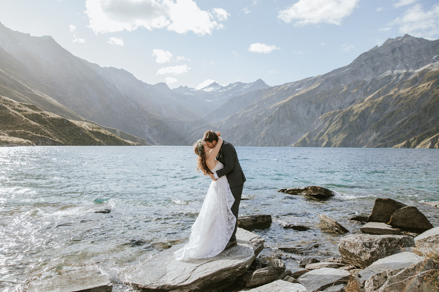 A couple share a kiss by a lake at Lochnagar on their Wanaka Elopement Wedding. They stand by a lake with mountains in the background. With photography by Alpine Image Company