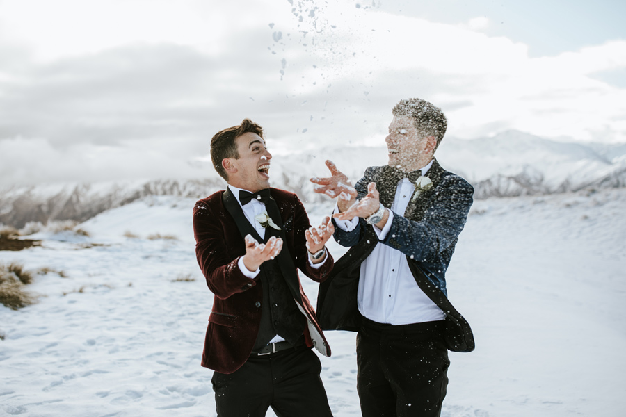 Two grooms throw snow and smile at each other on their Queenstown Elopement Wedding. With photography by Alpine Image Company