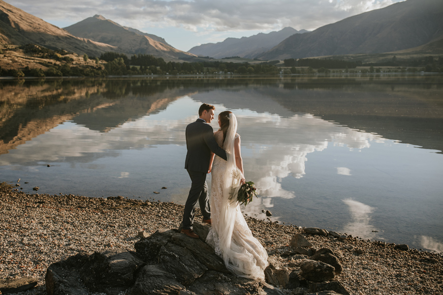 A bride and groom look out at a glassy lake, on their Wanaka Elopement Wedding day. The mountains in the distance are reflected in the lake. With photography by Alpine Image Company