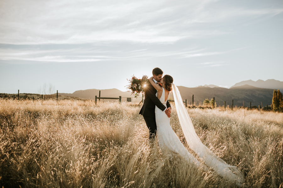 A couple kiss in a golden field on their Wanaka Elopement Wedding. With photography by Alpine Image Company