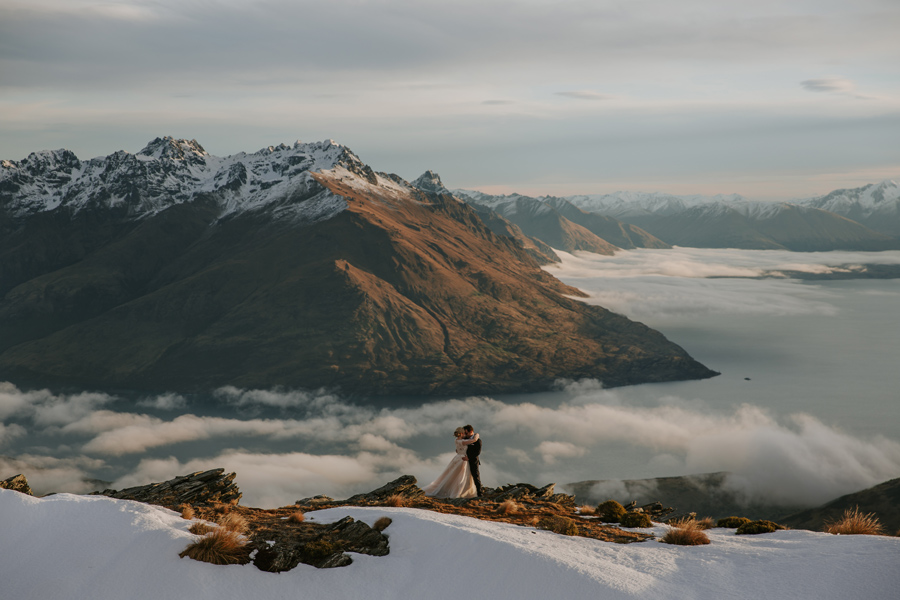 A bride and groom embrace on The Remarks on their Queenstown Elopement Wedding. They stand on a ridgeline in front of a lake, with snow capped mountains in the background. With photography by Alpine Image Company