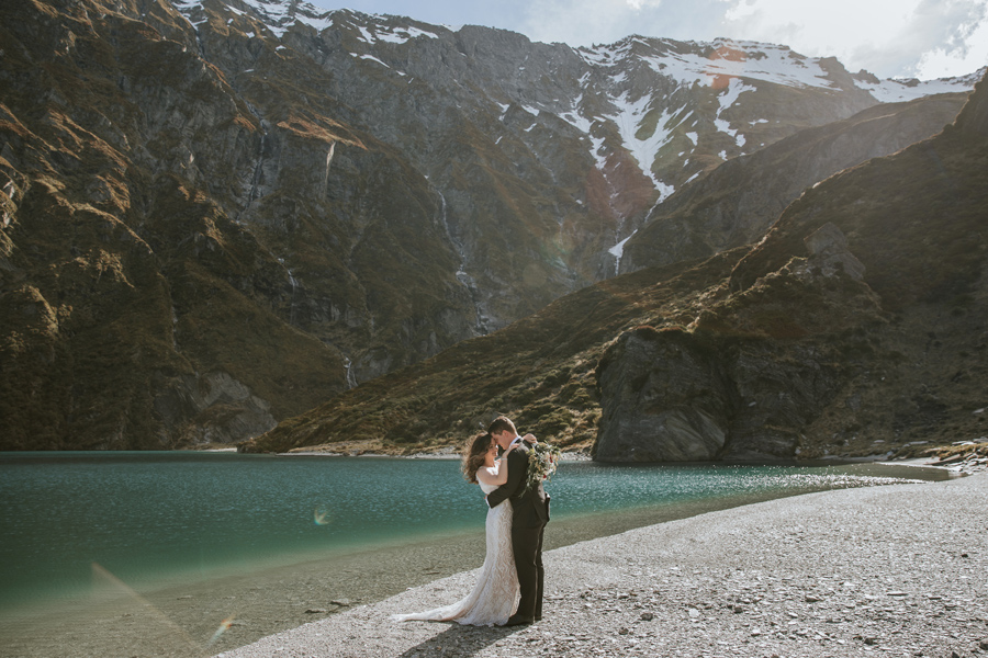 A bride and groom embrace infront of a valley at Earnslaw Burn, on their Wanaka Elopement Wedding. There are snowcapped mountains towering behind them, and they stand by a lake. With photography by Alpine Image Company