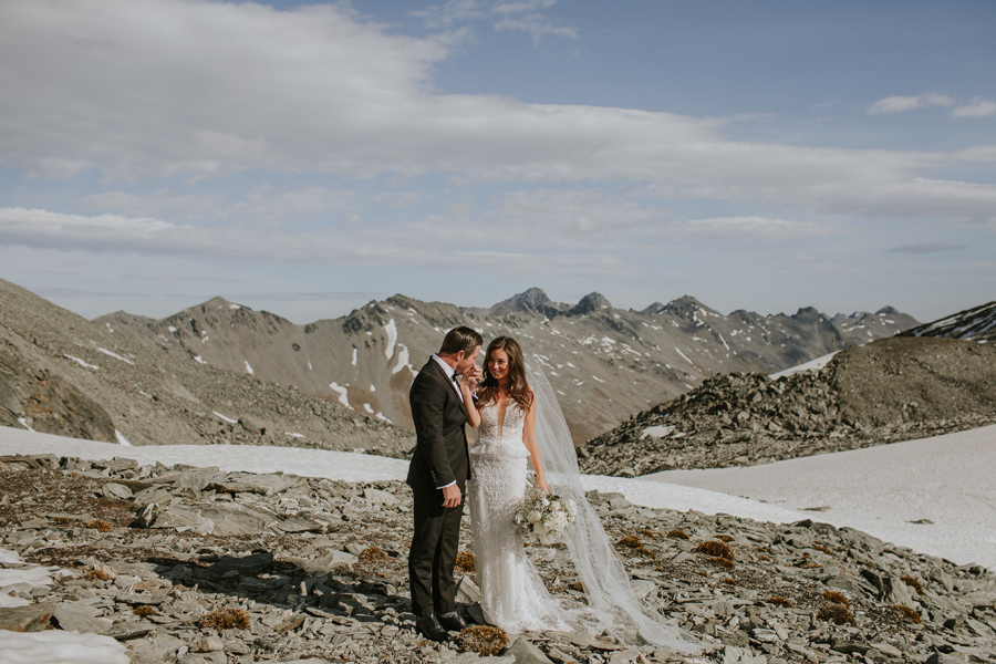 A groom kisses his brides hand on their Queenstown Elopement wedding. They are standing on Double Cone, on The Remarks. There are rocky mountains and snow in the background. The sky is blue. With photography by Alpine Image Company