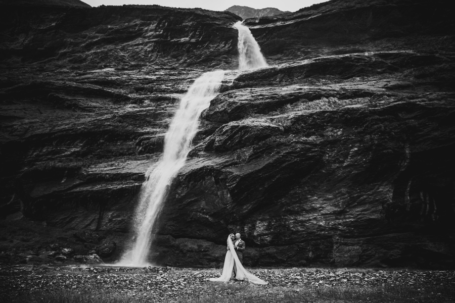 A couple embrace beside a large waterfall at Earnslaw Burn on their Queenstown Elopement Wedding. The image is black and white. With photography by Alpine Image Company