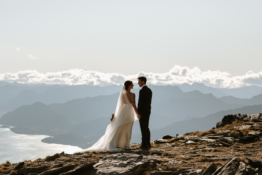 A couple stand on The Remarkables on their Queenstown Elopement Wedding day. There are mountains in the background, and the sky is blue. With photography by Alpine Image Company