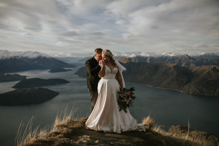 A couple stand on the point of Coromandel Peak. There are snowcapped mountains in the distance and a lake. The bride kisses the grooms hand, on their Wanaka Elopement Wedding. With photography by Alpine Image Company