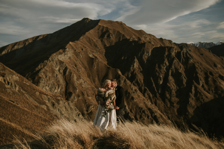 A couple embrace in the last of the sunlight, on Coromandel Peak, on their Wanaka Elopement Wedding. There is a shadowed mountain in the background, and the grass that they are standing in is long. With photography by Alpine Image Company