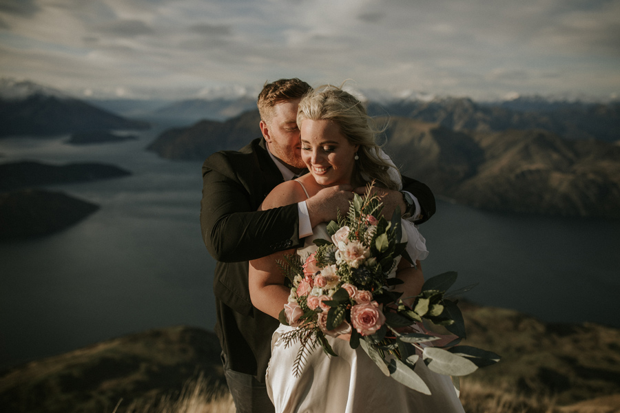 A groom embraces his bride on their Wanaka Elopement Day, on Coromandel Peak. There are mountains and a lake in the distance. With photography by Alpine Image Company