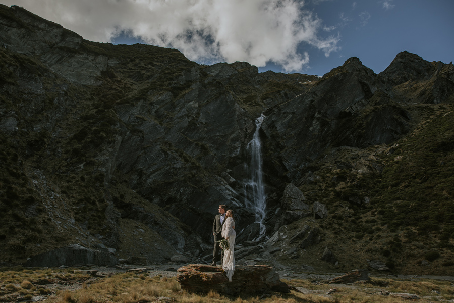 A couple stand in front of a waterfall at Lochnagar on their Queenstown Elopement Wedding. With photography by Alpine Image Company