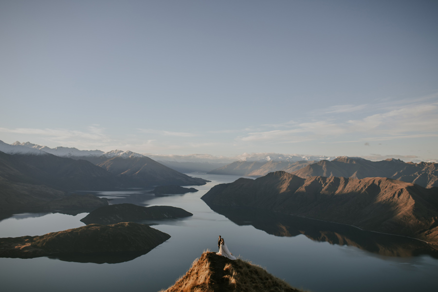 A couple stand on coromandel peak on their wanaka elopement wedding day. The lake behind them is calm, and the mountains in the distance have snow on them. With photography by Alpine Image Company