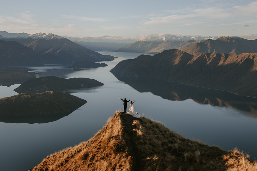 A couple throw their arms in the air in happiness on their Wanaka Elopement Wedding day. They stand on Coromandel Peak. There are mountains in the distance and the lake is calm. With photography by Alpine Image Company