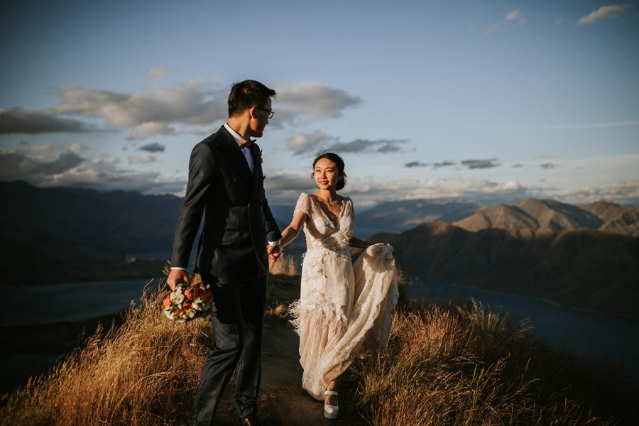 A couple walk along a mountaintop on their wanaka elopement day. The sky is blue and the grass is golden. With photography by Alpine Image Company