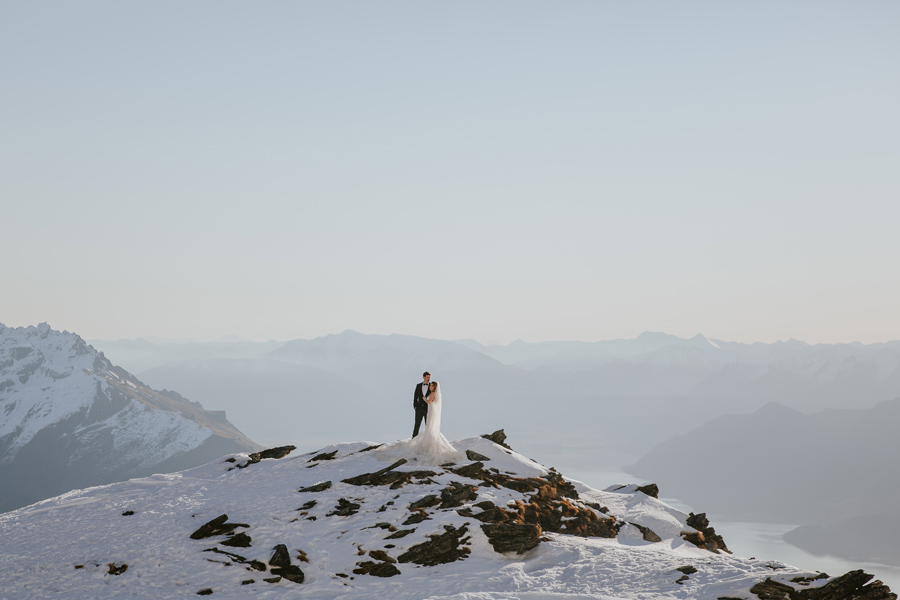 A couple embrace on a snowy mountain top. There are snow capped mountains in the distance, and the sky is blue. With photography by Alpine Image Company