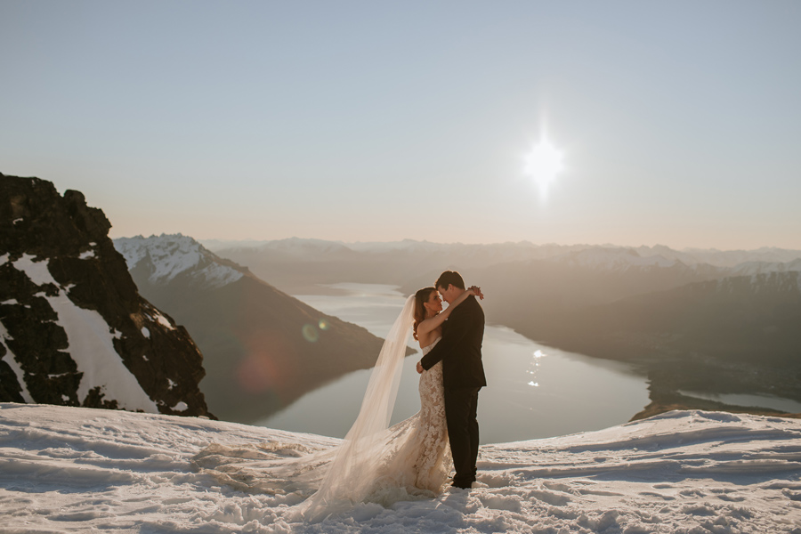 A bride and groom embrace and look at each other, as they stand on a snow capped mountain on their Queenstown Elopement day. There are mountains in the distance and the sky is blue. With photography by Alpine Image Company