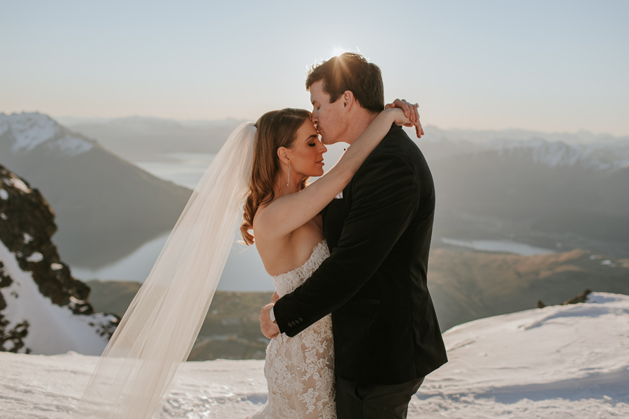 A groom kisses his bride on the head, on their Queenstown elopement wedding. They are standing on a snow capped mountain, with mountains and a lake in the distance. With photography by Alpine Image Company