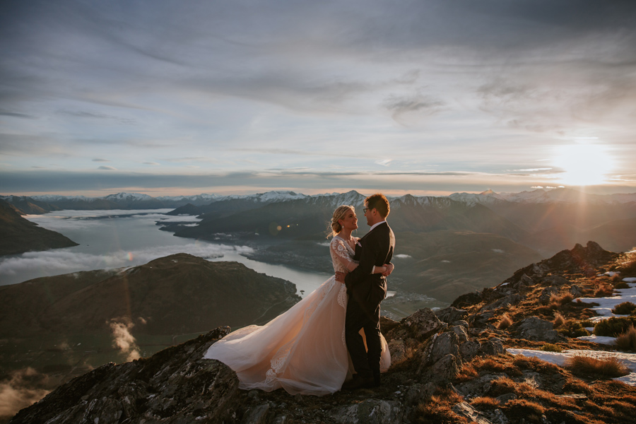 A bride and groom embrace on a mountain, on their Queenstown elopement wedding. There are mountains in the distance and the sun is setting. With photography by Alpine Image Company