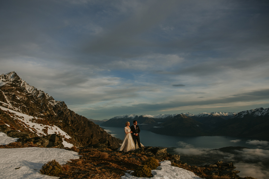 A bride and groom look out at the view, as they stand on a mountain on their Queenstown Elopement wedding day. There is snow around them, and the mountains behind them are snow capped too. With photography by Alpine Image Company